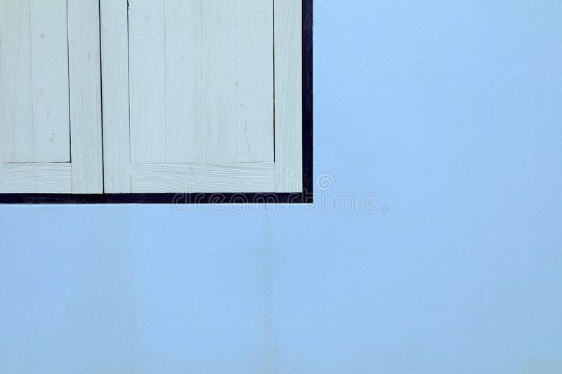 在油漆蓝色混凝土墙上的木窗口 库存照片