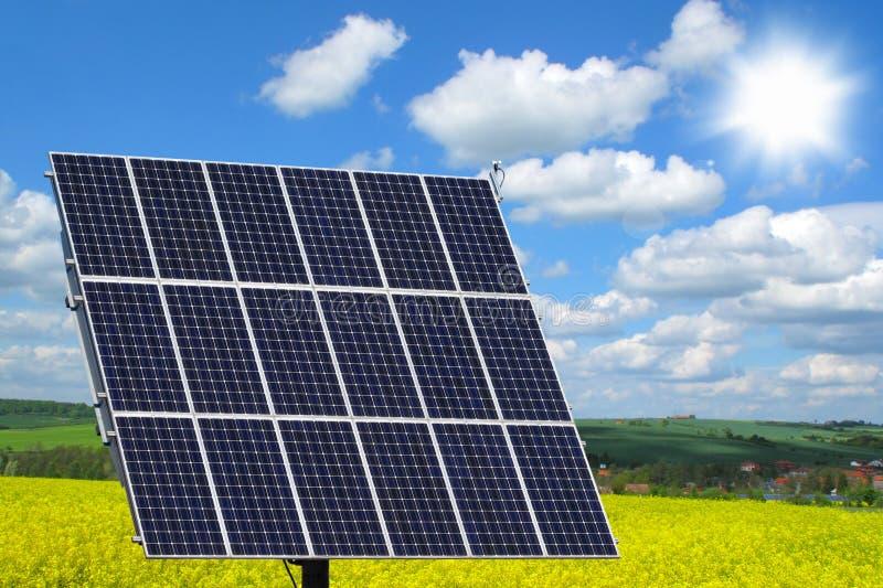 在油菜籽领域的太阳电池板 免版税库存照片