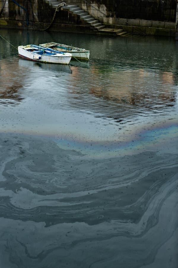 在油造成的码头的水污染 库存照片