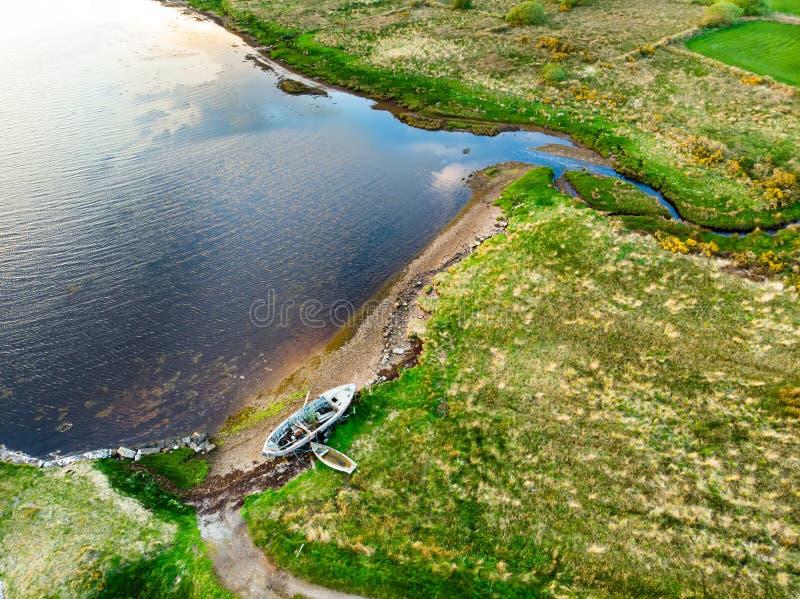 在沿凯利路线圆环的一个小海滩的老小船  在日落,凯里郡的Iveragh半岛坚固性海岸, 免版税库存照片