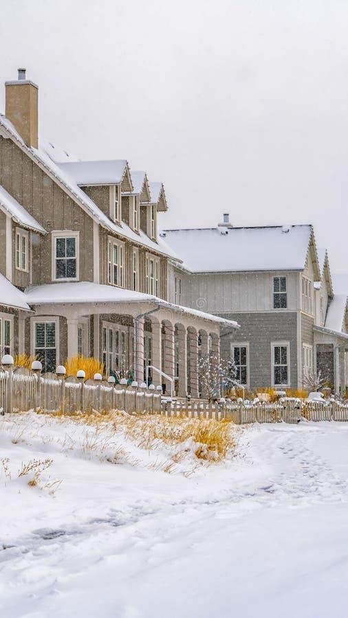 在沿房子的积雪的地面铭记的垂直的足迹在冬天季节期间 免版税库存照片