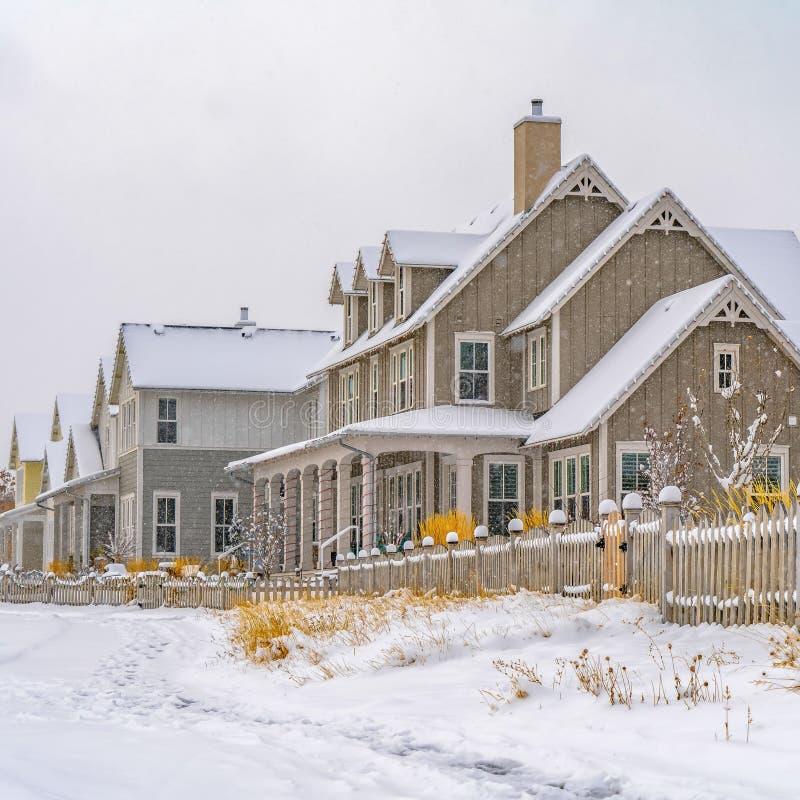 在沿房子的积雪的地面铭记的清楚的方形的足迹在冬天季节期间 库存照片