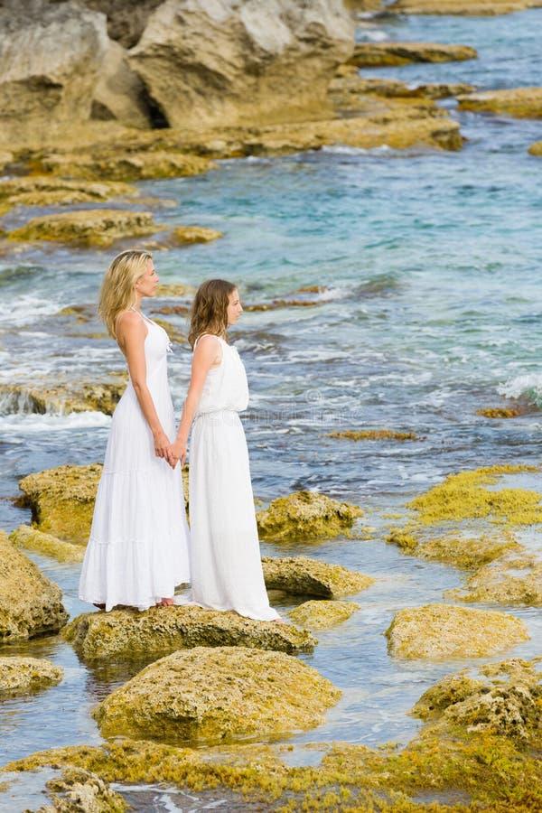 在沿海岩石的美好的白肤金发的母亲和女儿立场在白色长的礼服 免版税库存照片
