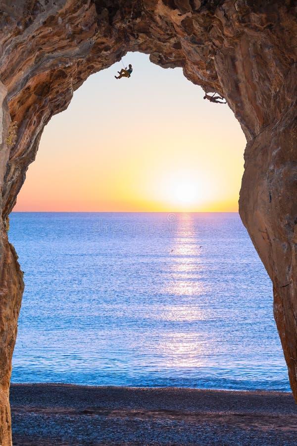 在沿海岸区的深高洞和日出的极端登山人 库存照片