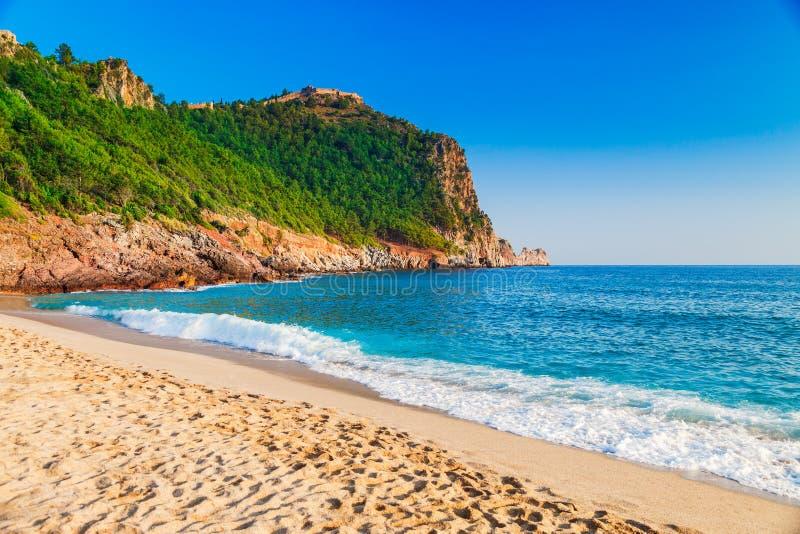 在沿海的帕特拉海滩与在阿拉尼亚半岛,安塔利亚区,土耳其的绿色岩石 旅游业的美好的晴朗的风景 库存照片