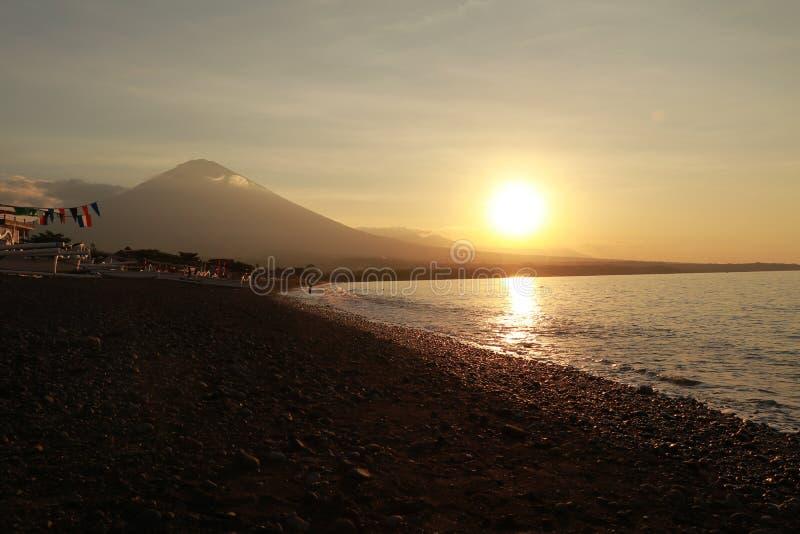 在沿海的浪漫日落在印度尼西亚 冲浪者去享用paddleboard在日落 有庄严火山的海岸线全景 免版税库存图片