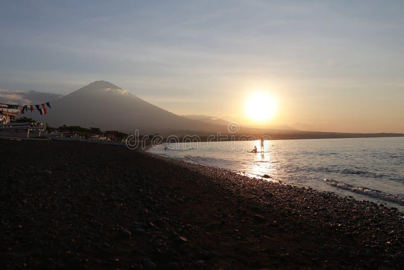 在沿海的浪漫日落在印度尼西亚 冲浪者去享用paddleboard在日落 有庄严火山的海岸线全景 免版税库存照片