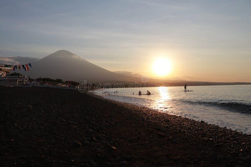 在沿海的浪漫日落在印度尼西亚 冲浪者去享用paddleboard在日落 有庄严火山的海岸线全景 库存照片