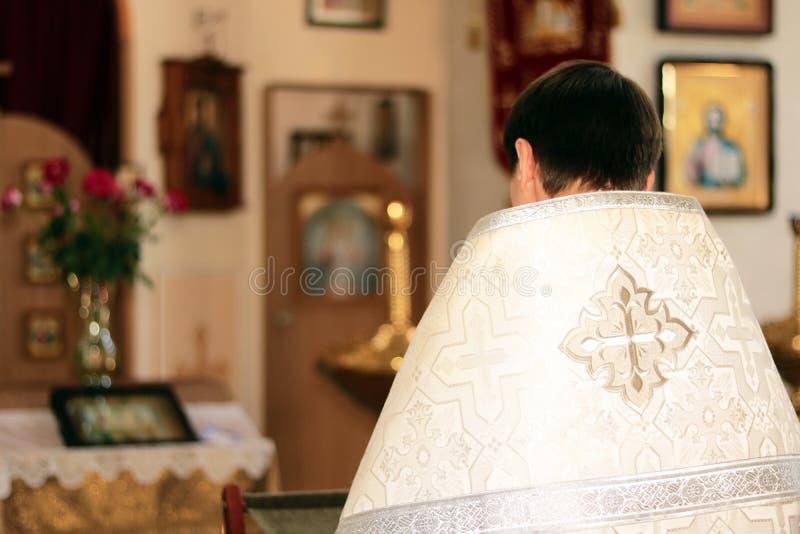 在法事期间,教士在教会读祷告 免版税库存照片