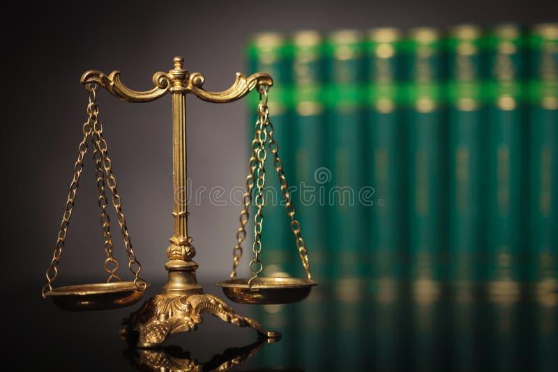 在法律书籍前面行的古色古香的金黄标度  免版税库存图片
