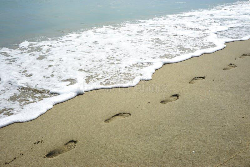 在泡沫似的波浪旁边的赤足脚印在一个原始沙滩在热带越南 免版税库存图片