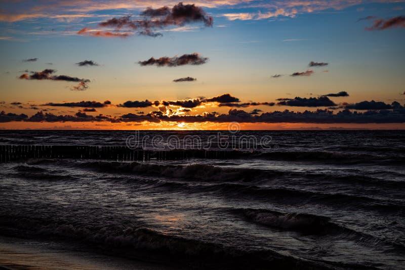 在波兰波罗的海的五颜六色的日落有黑暗的天空云彩和防堤的 免版税库存照片
