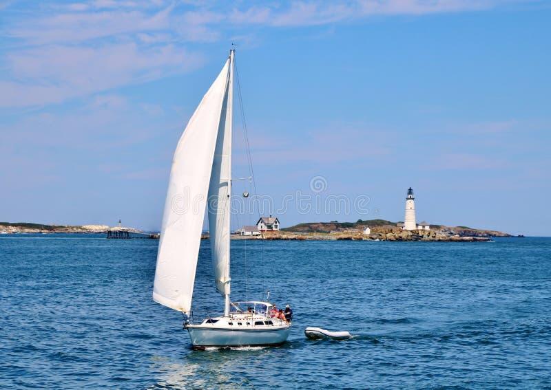 在波士顿港口灯塔前面的游艇航行 免版税库存图片