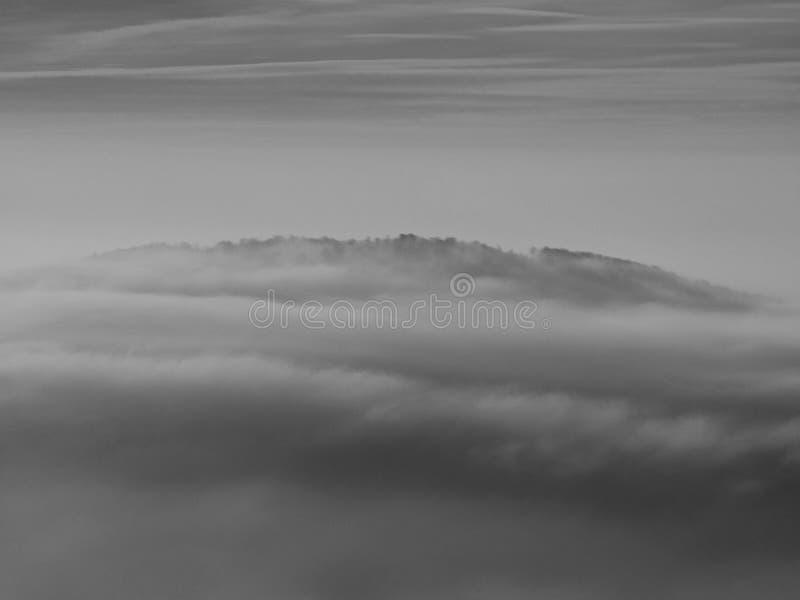 在波希米亚的一座美丽的山的秋天日出。从雾增加的小山峰顶。 库存照片