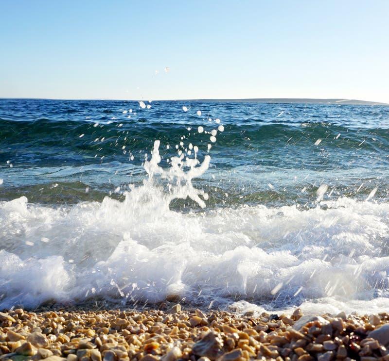在波浪拍打的上面的白海对岸的泡沫和Pebble海滩飞溅和表面  图库摄影