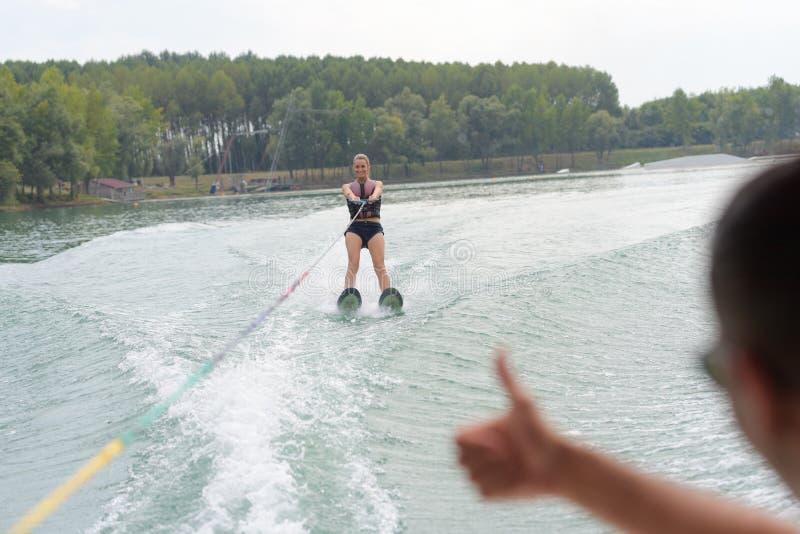 在波浪汽艇的妇女骑马在夏天湖 库存照片
