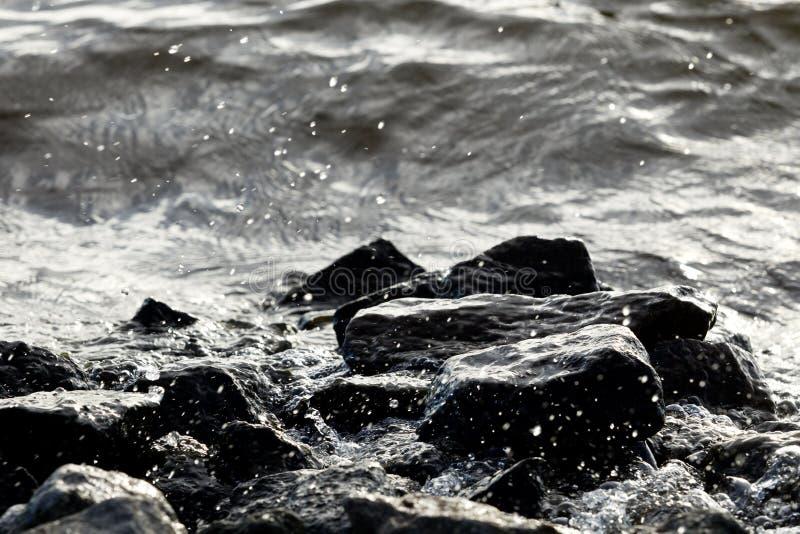 在波浪背景的沿海岩石 库存照片