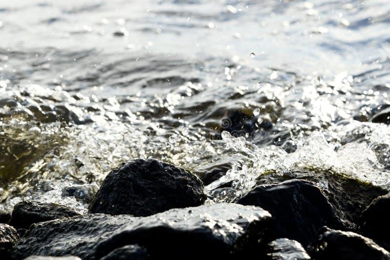 在波浪背景的沿海岩石 免版税图库摄影