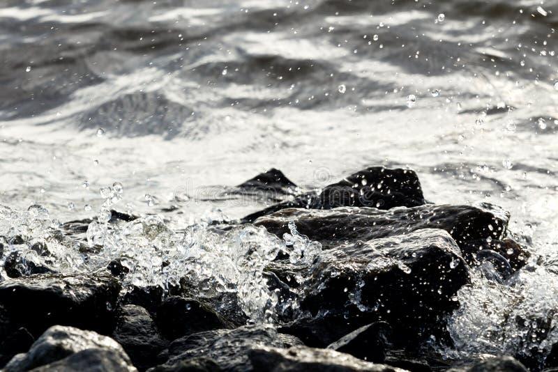 在波浪背景的沿海岩石 免版税库存照片