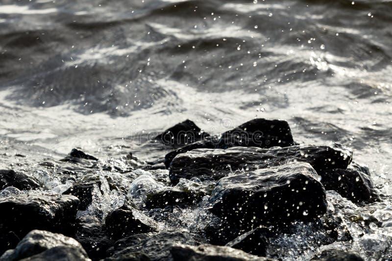 在波浪背景的沿海岩石 库存图片