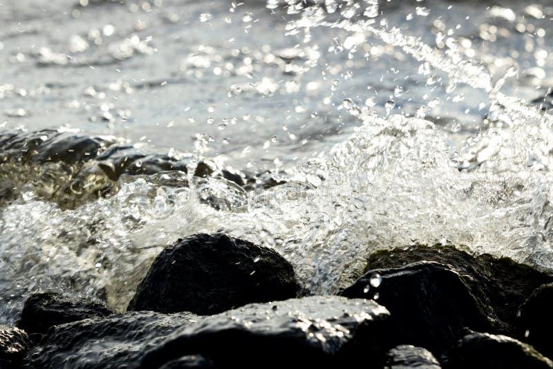 在波浪背景的沿海岩石 免版税库存图片