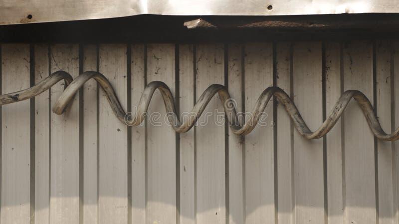 在波状钢墙壁上的巨型肮脏的螺旋电线 免版税库存照片
