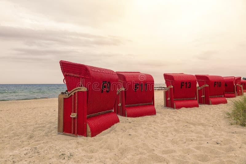 在波罗的海海岸的红色戴头巾海滩睡椅 免版税库存照片