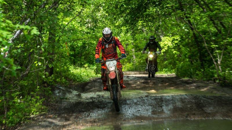 在泥的Enduro moto与大飞溅 免版税库存图片