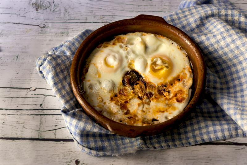 在泥罐的煎蛋在白色木背景 免版税图库摄影