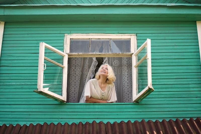 在注视着面对日出早晨的窗口附近的妇女 库存照片