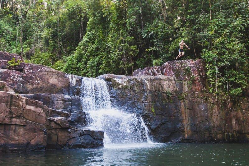在泰国供以人员跳跃到在酸值库特海岛上的瀑布 库存图片