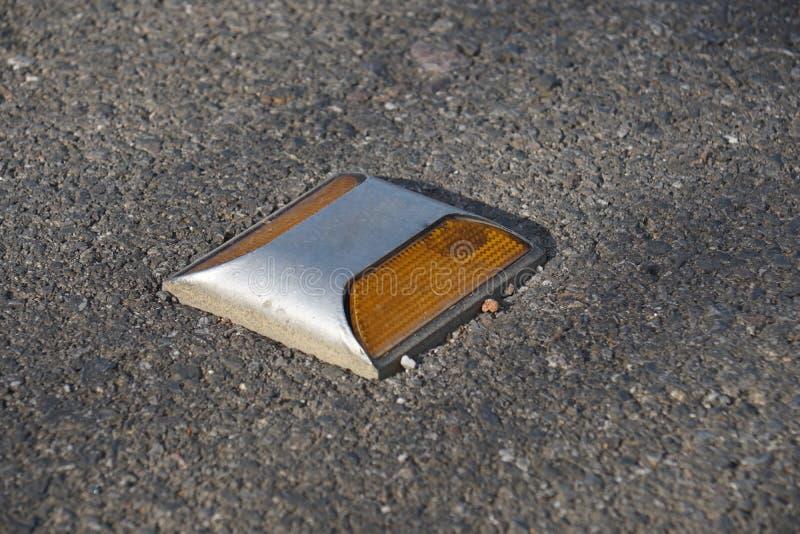 在泰国金属化有黄色反射器的路螺柱在柏油路 库存照片