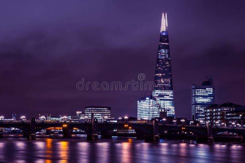 在泰晤士河的现代伦敦地平线在与碎片buildi的晚上 库存图片