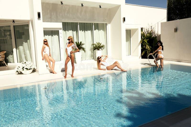 在泳装的美好的模型,摆在豪华游泳poo附近 库存照片
