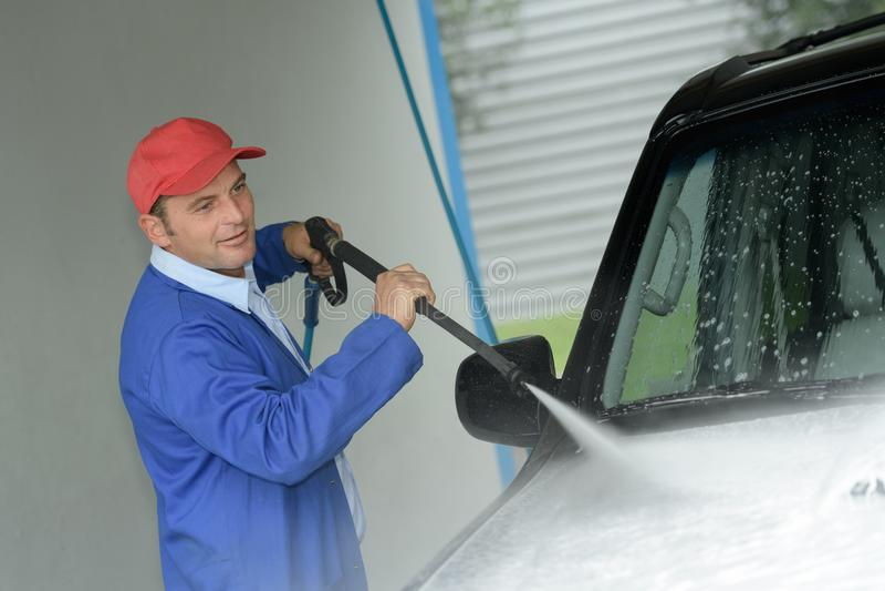 在洗车的人工作者洗涤的汽车 免版税库存照片