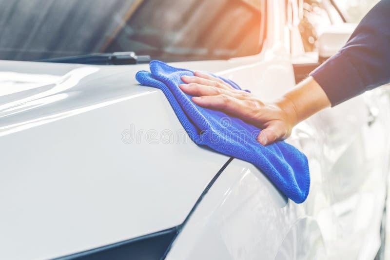 在洗车的工作者擦亮的汽车 免版税库存照片
