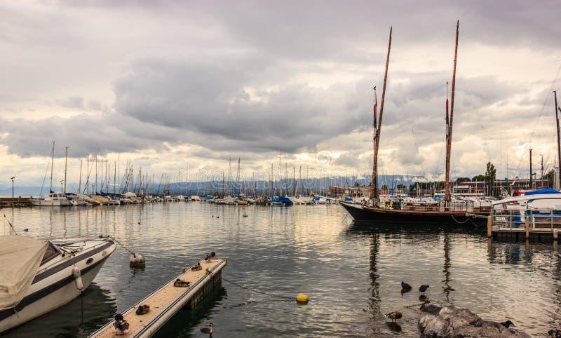 在洛桑小游艇船坞的美好的日落视图有在莱芒湖,洛桑Ouchy的游艇的渔村,瑞士,欧洲 免版税库存照片