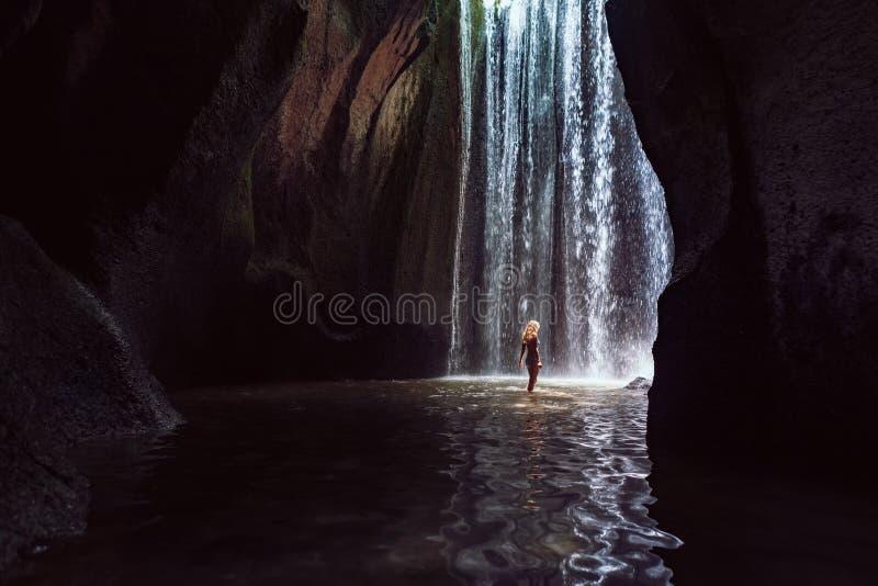 在洞瀑布下的妇女立场 免版税库存照片