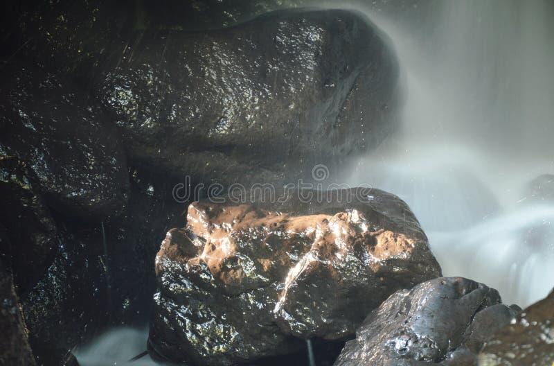 在洞的瀑布在岩石后在森林里 免版税库存照片