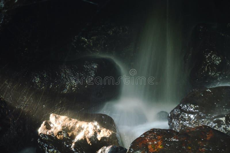 在洞的瀑布在岩石后在森林里 库存图片