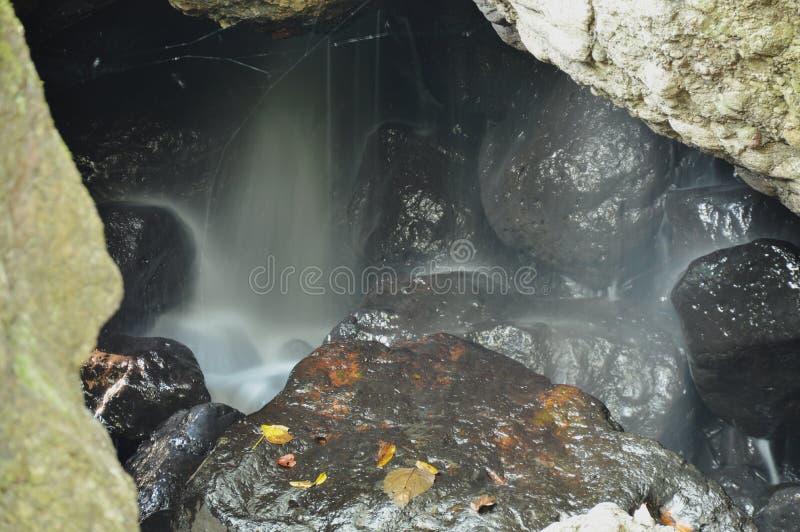 在洞的瀑布在岩石后在森林里 库存照片