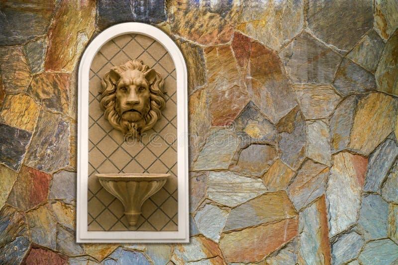 在洞穴状石墙上的狮子顶头雕象 概念装饰建筑学雕塑浅浮雕装饰品 库存图片