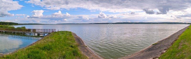 在洪泛区的一座狭窄的桥梁以一个宽深湖为背景 免版税库存照片