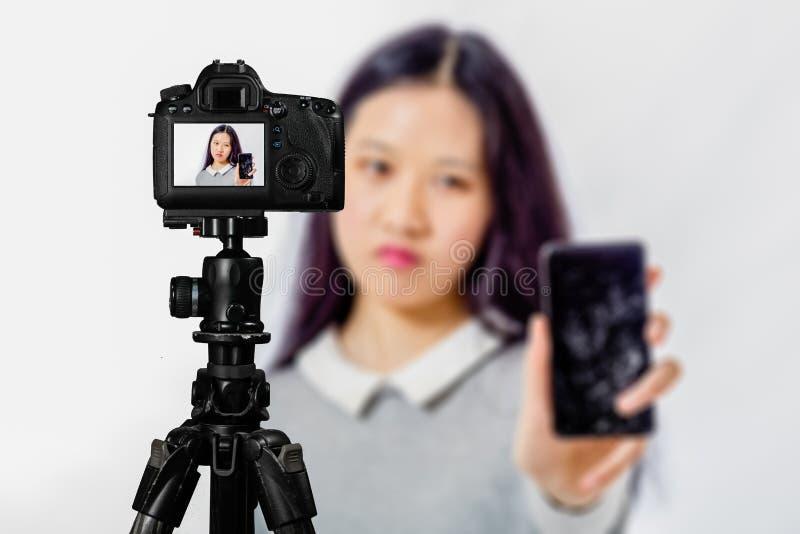 在活看法的焦点在三脚架,有被弄脏的场面的十几岁的女孩的照相机在背景中 少年vlogger livestreaming的展示 库存照片