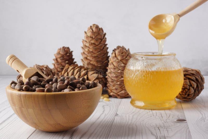 在流动从一把木匙子的碗和蜂蜜的松果入在轻的背景的一个玻璃罐在雪松锥体旁边 库存照片