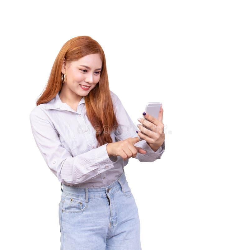 在流动智能手机的快乐的逗人喜爱的美好的年轻亚洲妇女用途手指接触,感觉愉快和惊奇隔绝在白色 免版税库存照片