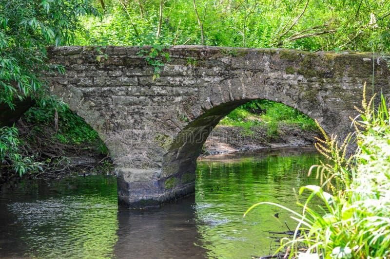 在流动的小河的桥梁 免版税库存照片