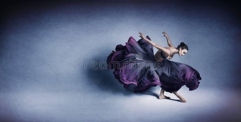 在流动的深蓝礼服的优美的妇女跳舞 免版税库存照片