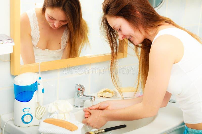 在流动的自来水下的妇女洗涤的手 免版税库存照片
