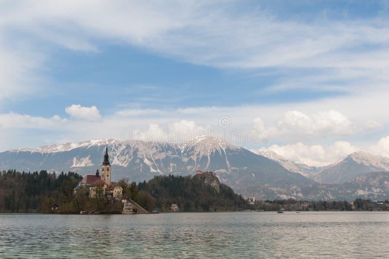 在流血的湖、海岛、教会和城堡的惊人的看法与山脉Stol, Vrtaca,在背景流血的Begunjscica, Sloveni 库存照片